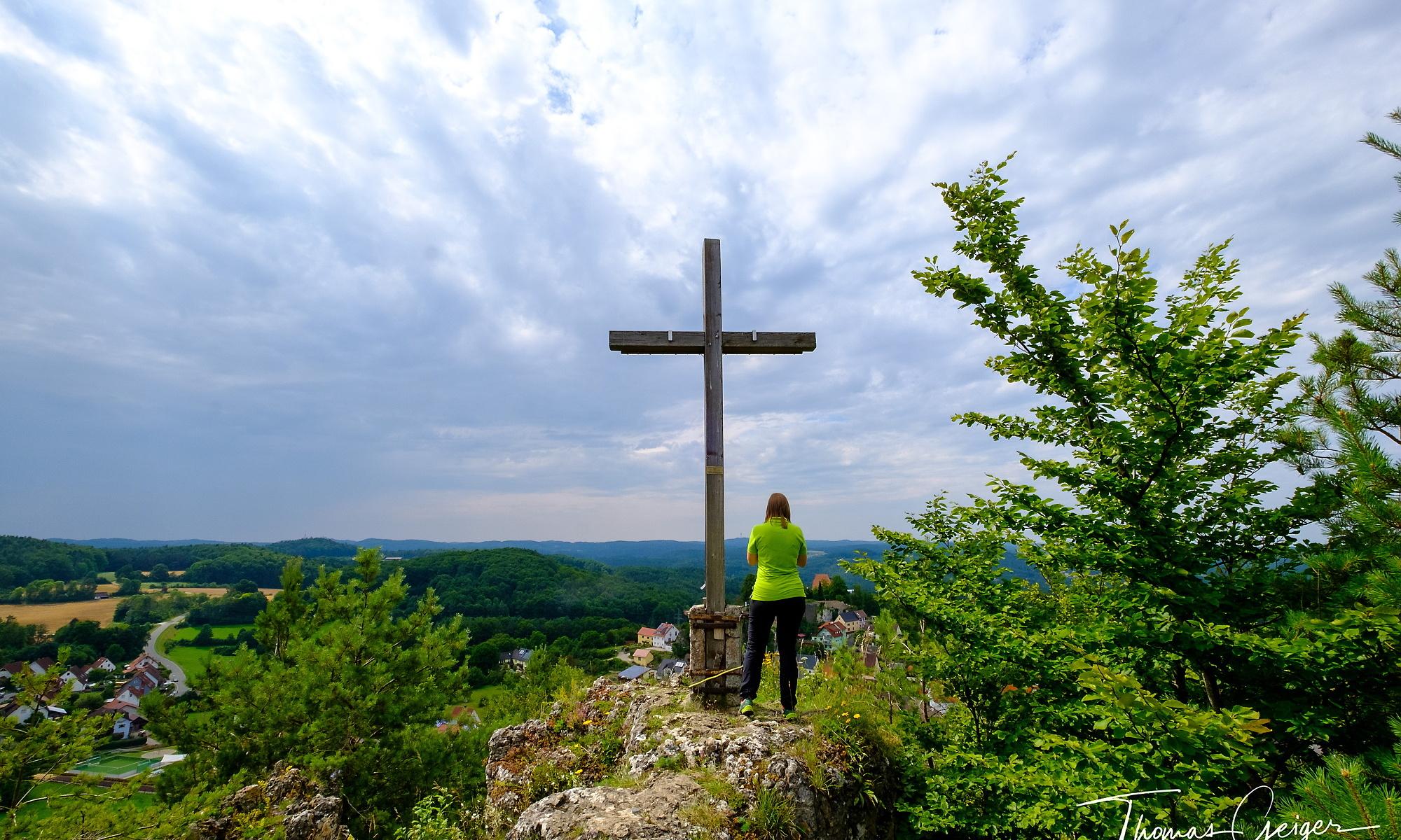 Frau steht an Gipfelkreuz und schaut in die Landschaft